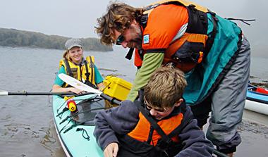 Bruce Helping a boy in a kayak.